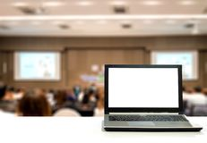 Laptop on white desk with blurred audience in seminar business a royalty free stock photos