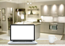 Laptop white screen and coffee cup on marble table with kitchen Stock Photos