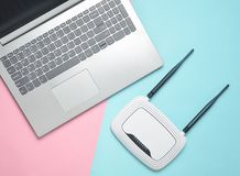 A laptop and a wi-fi router on a colored paper background. Keyboard, touchpad. Modern digital technologies. Copy space. Top view stock photography