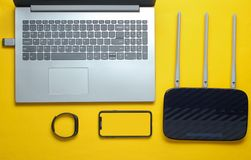 Laptop, wi-fi router, smartphone, smart tracker. On yellow background. Online work, gadgets for modern people stock photos