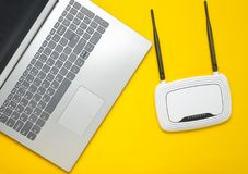 A laptop and a wi-fi router on a yellow paper background. Keyboard, touchpad. Modern digital technologies. Copy space. Top view stock photo