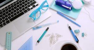 Laptop, widowiska, pióro, kawa, papierowa klamerka, skala, setu kwadrat i hełmofony na białym tle 4k, zdjęcie wideo