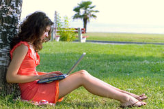 Laptop woman. Young woman sitting on the grass with laptop on her knees Royalty Free Stock Photos