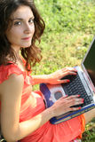 Laptop woman. Young woman sitting on the grass with laptop on her knees Stock Photos