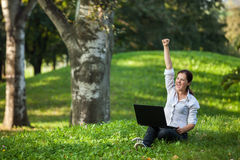 Laptop woman. Excited mature woman wining holding fist up high screaming of happiness with laptop Royalty Free Stock Photo