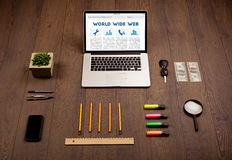 Laptop on wooden desk with office suplies Royalty Free Stock Photo