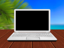 Laptop on wooden desk with riviera coast in background Stock Image