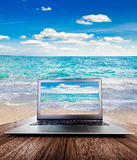 Laptop on wooden desk, view on the sea Royalty Free Stock Photography