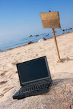 Laptop and wooden sign on beach. Black laptop in front on rock and wooden sign in back at seaside Royalty Free Stock Photo