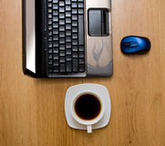 Laptop on wooden table. Laptop, mice and cup of coffee on wooden table royalty free stock photo
