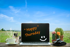 Laptop on wooden table, Happy Thursday. Text on screen royalty free stock photos