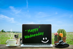 Laptop on wooden table, Happy Wednesday. Text on screen royalty free stock images