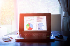 Laptop on wooden table showing charts and graph against office b Royalty Free Stock Image