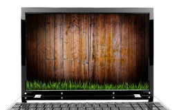 Laptop with wooden wall and grass Royalty Free Stock Photography