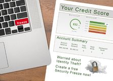 Laptop with the word Freeze on key with credit report. Laptop with Freeze on the red key by credit score report as concept for new law allowing free credit stock images