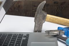 Laptop and work tools. On the white surface of the table is a tablet, skein, chisel and pliers. Destruction and repair of electron. Ic devices Stock Photography