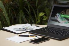 Laptop z dolarami i telefon na stole na tle zdjęcie royalty free