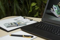 Laptop z dolarami i telefon na stole na tle zdjęcia stock