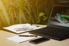Laptop z dolarami i telefon na stole na tle fotografia royalty free