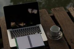 Laptop z filiżanką na drewnie jesień tła ptaków lota zieleń opuszczać słońce zwrot promieniom Obrazy Stock