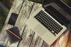 Laptop z notatnikiem, telefonem i hełmofonami, Obraz Royalty Free