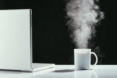 Laptop z parującą filiżanką herbata na stole Fotografia Stock