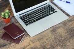 Laptop z paszporta notatnikiem i książkami fotografia stock