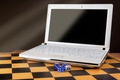 Laptop z pustym ekranem i dices na drewnianym chessboard Zdjęcie Stock
