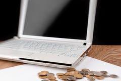 Laptop z pustym ekranem i rozsypiskiem monety na drewnianym stole Obraz Stock