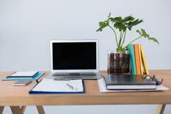 Laptop z telefonem komórkowym, schowkiem, dzienniczkiem i piórem na stole, Zdjęcie Stock