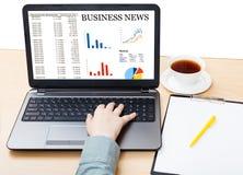 Laptop z wiadomości gospodarcze na ekranie na biurowym biurku Zdjęcia Stock