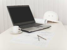 Laptop, Zeichnungen, Sturzhelm und Kompassse auf Tabelle stockbilder