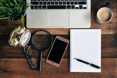 Laptop, zielona roślina, zegar, powiększa - szkło, telefon, kawa i puste miejsce notatnik na drewnianym stole, obrazy royalty free