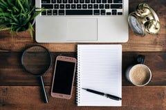Laptop, zielona roślina, zegar, powiększa - szkło, telefon, kawa i puste miejsce notatnik na drewnianym stole, Fotografia Royalty Free