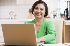 laptopa kuchenne kobieta uśmiechnięta Obraz Stock