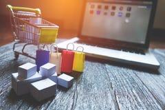 Laptopleerer bildschirm und -hopfen karren voll von den Geschenken mit copyspac stockfotos