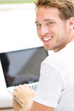 Laptopmannlächeln glücklich unter Verwendung des Computers draußen Stockfotografie