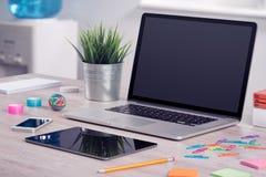Laptopmodell mit Tablet-Computer und Smartphone auf Schreibtisch stockfotos