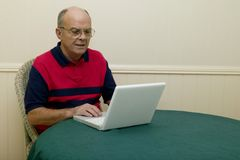 Laptops. View of a senior male using a laptop sitting at a table Royalty Free Stock Photo