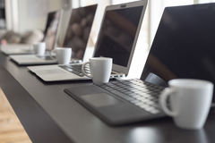 Laptops and espresso lined up side view Royalty Free Stock Photography