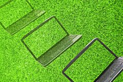 Laptops fading out of  grass Stock Photography