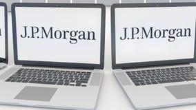 Laptops with J.P. Morgan logo on the screen. Computer technology conceptual editorial 4K clip, seamless loop. Laptops with J.P. Morgan logo on the screen stock video
