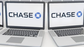 Laptops with JPMorgan Chase Bank logo on the screen. Computer technology conceptual editorial 4K clip, seamless loop. Laptops with JPMorgan Chase Bank logo on stock video