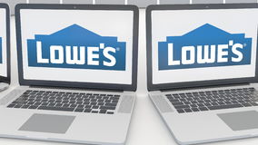 Laptops with Lowe`s logo on the screen. Computer technology conceptual editorial 4K clip, seamless loop. Laptops with Lowe`s logo on the screen. Computer stock video