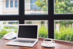 Laptops met witte koffiemok op houten bureau Royalty-vrije Stock Afbeeldingen