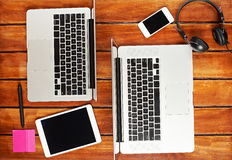 Laptops of people working together. On wooden table view from top. Electronics on wooden table two laptops, smartphone,table,earphones royalty free stock photo