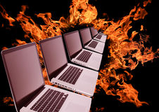 Laptops row in fiery ring. On black background Stock Images