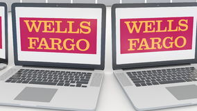 Laptops with Wells Fargo logo on the screen. Computer technology conceptual editorial 4K clip, seamless loop. Laptops with Wells Fargo logo on the screen stock video