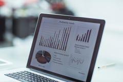Laptopschirm mit Finanzdiagramm auf einem Arbeitsplatz des Geschäftsmannes Stockfotografie