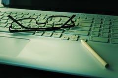 Laptoptastatur, Bleistift und schwarze Gläser Die goldene Taste oder Erreichen für den Himmel zum Eigenheimbesitze Sel Lizenzfreie Stockfotografie